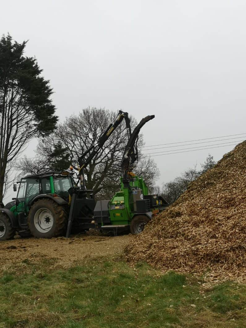 Crane fed chipper chipping wood